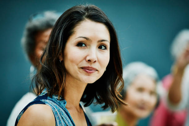 portrait of smiling mature woman at family dinner party in backyard - classy asian woman stock pictures, royalty-free photos & images