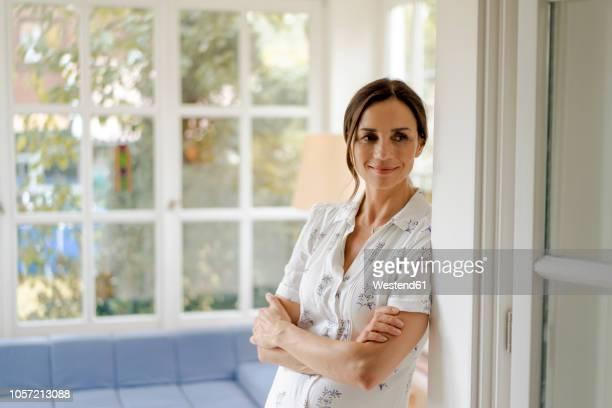 portrait of smiling mature woman at home - capelli castani foto e immagini stock