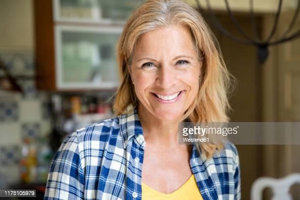 portrait of smiling mature woman at home - 45 49 jahre stock-fotos und bilder