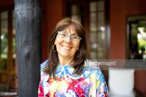 portret van lachende rijpe vrouw thuis - 55 59 jaar stockfoto's en -beelden