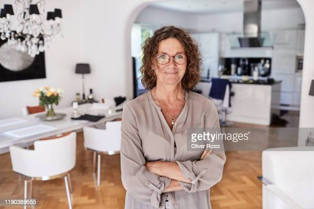 portrait of smiling mature woman at home - one mature woman only stock pictures, royalty-free photos & images