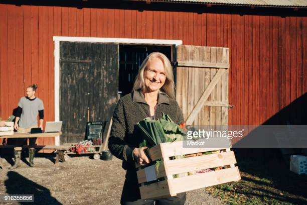 portrait of smiling mature woman carrying crate full of vegetables with barn in background - markt stockfoto's en -beelden