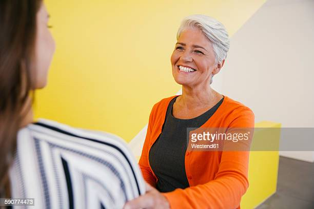 Portrait of smiling mature woman greeting another woman in an office