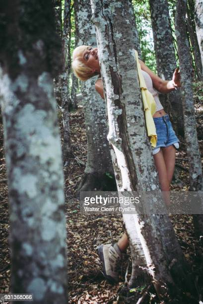Portrait Of Smiling Mature Woman Hiding Behind Trees In Forest