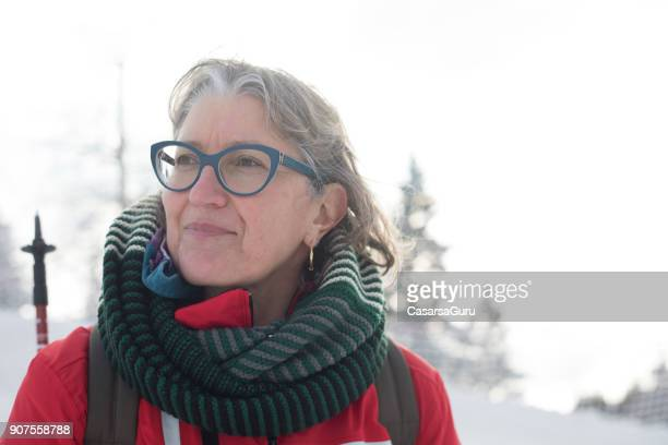 portrait of smiling mature woman hiking on snowed mountain - one mature woman only stock pictures, royalty-free photos & images