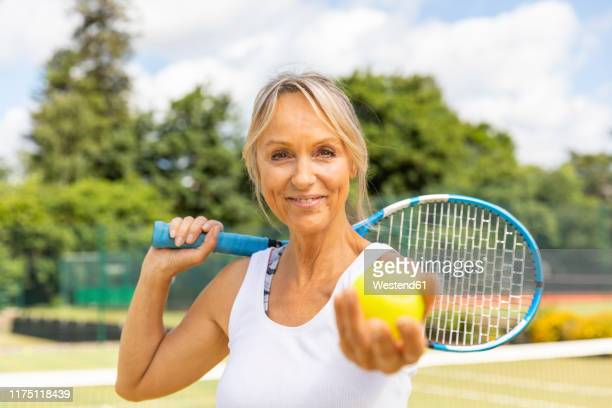 portrait of smiling mature woman holding a tennis ball at tennis club - tennis player stock pictures, royalty-free photos & images