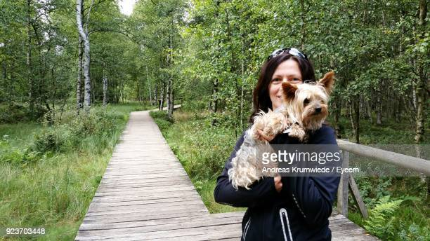 Portrait Of Smiling Mature Woman Holding Dog On Boardwalk In Forest