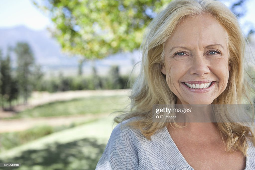 Portrait of smiling mature woman in park : Stock Photo