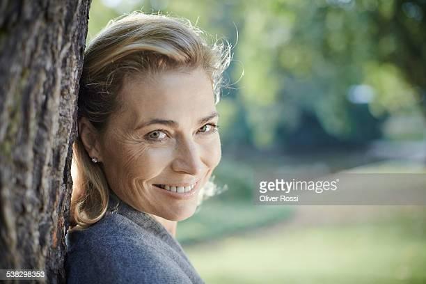 portrait of smiling mature woman in park - 50 54 jahre stock-fotos und bilder