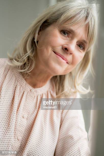 Portrait of smiling mature woman leaning against windowpane