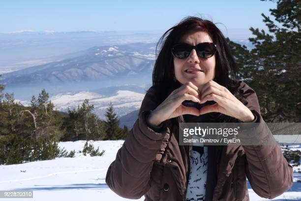 Portrait Of Smiling Mature Woman Making Heart Shape While Standing On Snow Field
