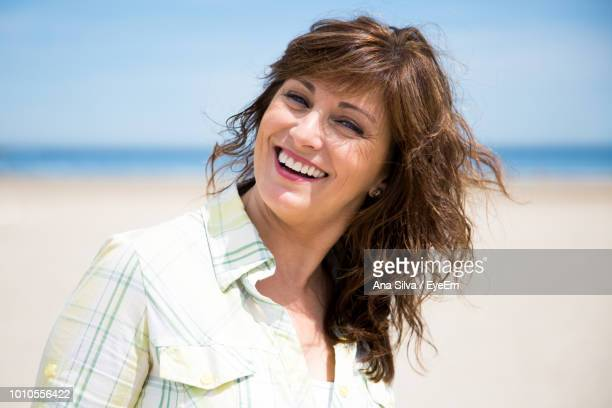 Portrait Of Smiling Mature Woman On Beach