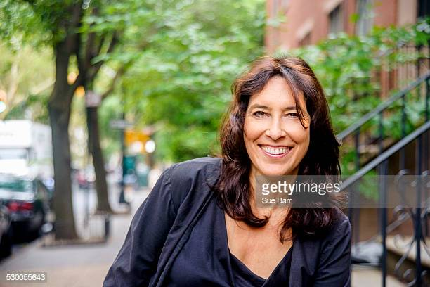 portrait of smiling mature woman on city street - 55 59 años fotografías e imágenes de stock
