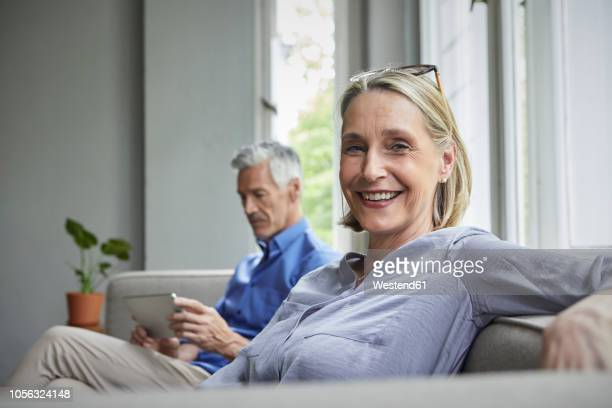 portrait of smiling mature woman on couch with man in background using tablet - ehefrau stock-fotos und bilder