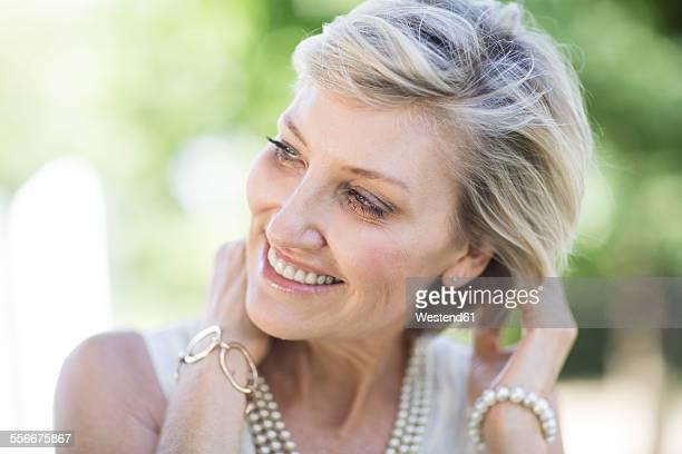 portrait of smiling mature woman outdoors - goed gekleed stockfoto's en -beelden