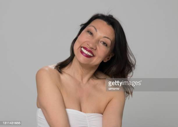 portret van glimlachende rijpe vrouw - strapless stockfoto's en -beelden