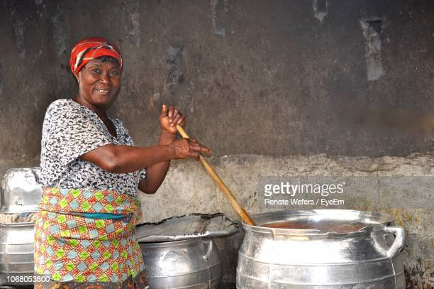 portrait of smiling mature woman preparing food in large container - gold coast stock pictures, royalty-free photos & images