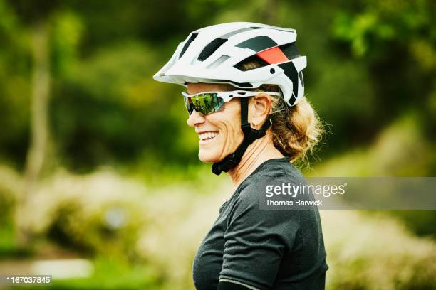 portrait of smiling mature woman relaxing after mountain bike ride with friends - sports helmet stock pictures, royalty-free photos & images