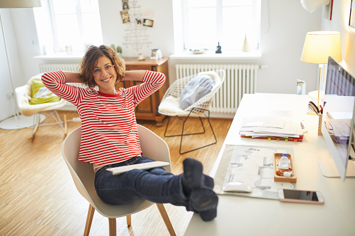 Portrait of smiling mature woman relaxing on armchair at home office - gettyimageskorea