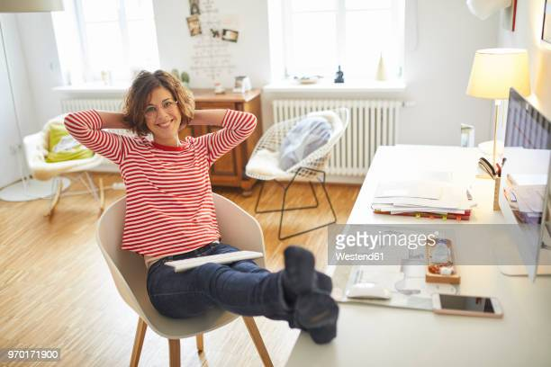 portrait of smiling mature woman relaxing on armchair at home office - hands behind head stock pictures, royalty-free photos & images