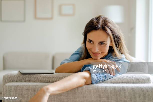 portrait of smiling mature woman resting on couch at home - sofa stock-fotos und bilder