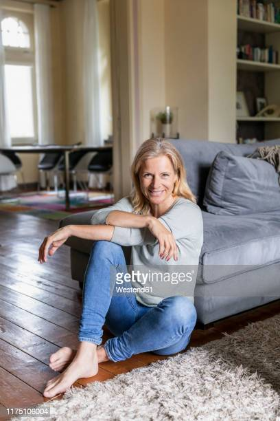 portrait of smiling mature woman siiting barefoot on the floor in the living room - sitting on ground stock pictures, royalty-free photos & images