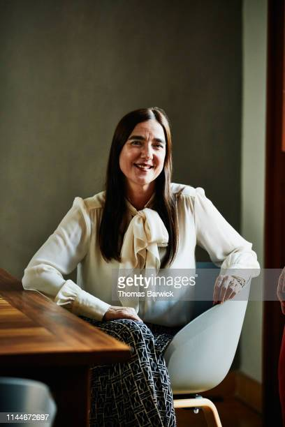 Portrait of smiling mature woman sitting at dining room table