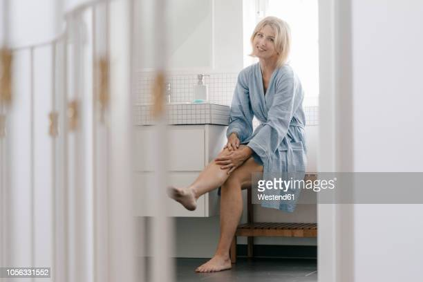 portrait of smiling mature woman sitting in bathroom touching her legs - jolies jambes photos et images de collection