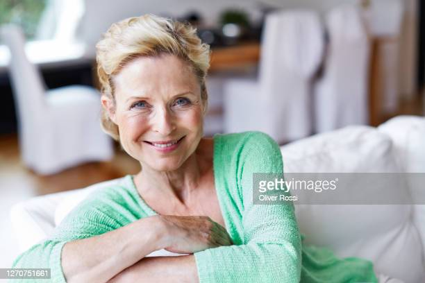 portrait of smiling mature woman sitting on couch at home - mature women stock pictures, royalty-free photos & images