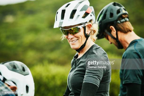 Portrait of smiling mature woman sitting on mountain bike before ride with friends