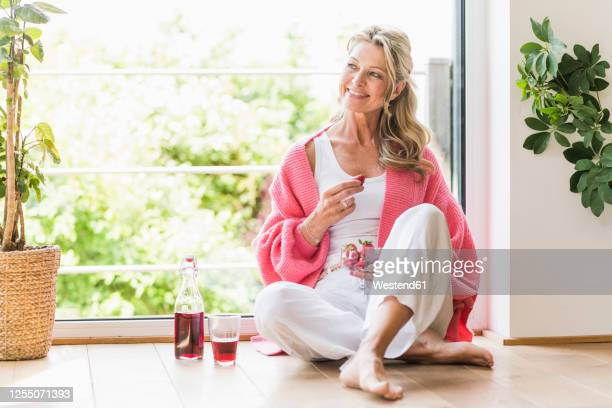 portrait of smiling mature woman sitting on the floor at home - beautiful people stock pictures, royalty-free photos & images