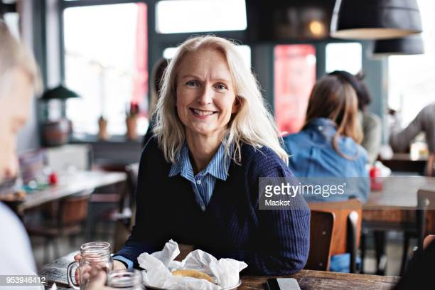 portrait of smiling mature woman sitting with man at dining table in restaurant - 50 59 years stock pictures, royalty-free photos & images