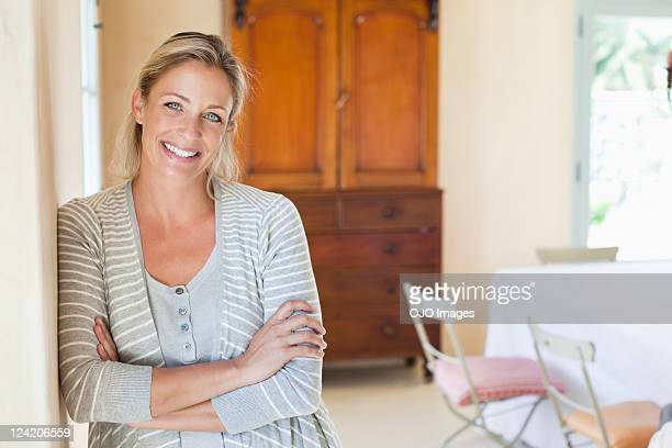 Portrait of smiling mature woman standing in living room