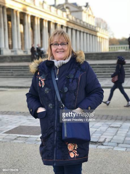Portrait Of Smiling Mature Woman Standing On Footpath