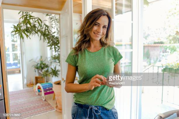 portrait of smiling mature woman using cell phone at home - 45 49 years stock pictures, royalty-free photos & images