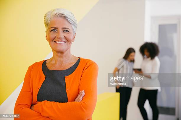 Portrait of smiling mature woman with crossed arms and two colleagues in the background