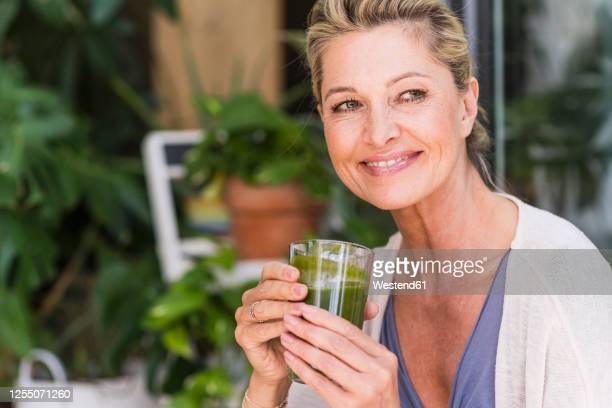 portrait of smiling mature woman  with enjoying green smoothie - one mature woman only stock-fotos und bilder
