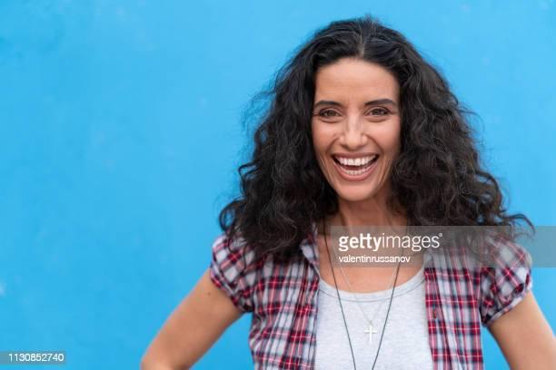 portrait of smiling mature women on blue background - portrait blue background stock pictures, royalty-free photos & images