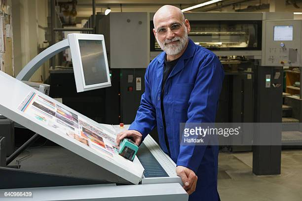 Portrait of smiling mature worker standing by equipment at printing press