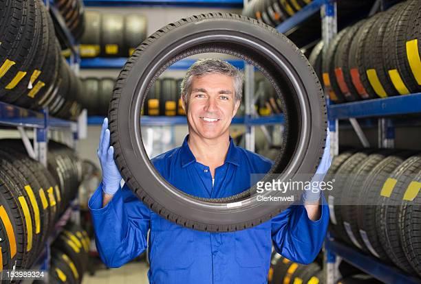 Retrato de sorrir mecânico segurando pneu em Oficina Automóvel