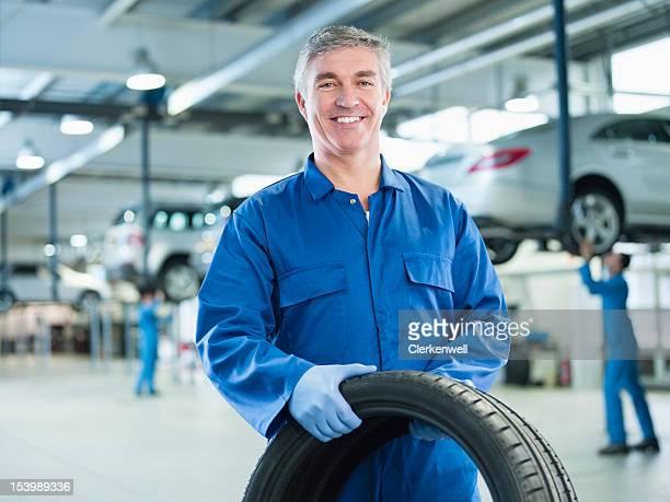Porträt von lächelnd Mechaniker hält Reifen Sie auto repair shop