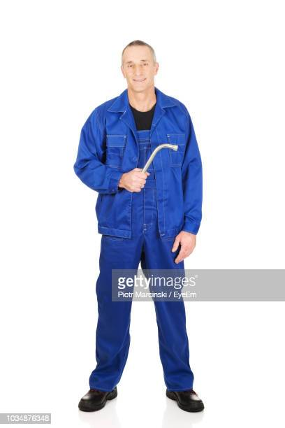 portrait of smiling mechanic holding work tool while standing against white background - coveralls stock pictures, royalty-free photos & images