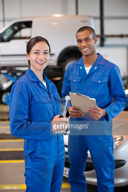 portrait of smiling mechanics in auto repair shop - coveralls stock pictures, royalty-free photos & images