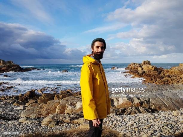 portrait of smiling mid adult bearded man standing on beach against sky - raincoat stock pictures, royalty-free photos & images