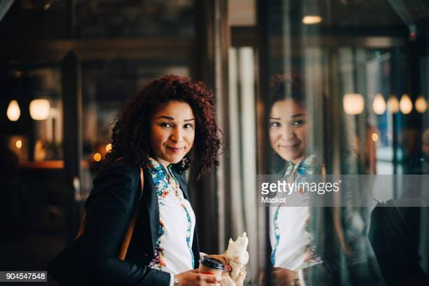 portrait of smiling mid adult businesswoman holding food and drink standing by window in cafe - une seule femme d'âge moyen photos et images de collection