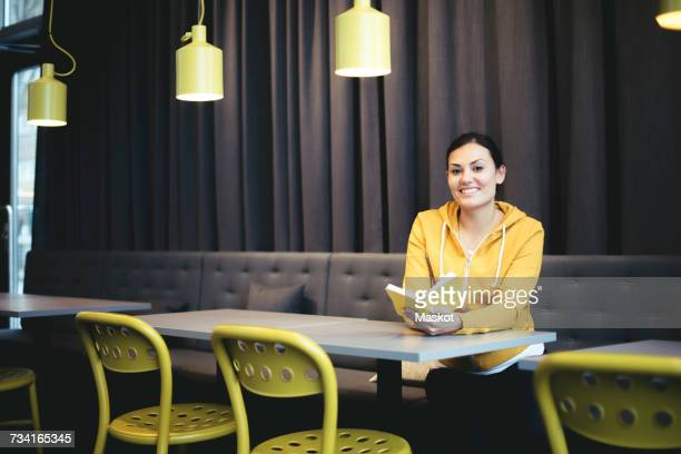 Portrait of smiling mid adult businesswoman with book in office cafeteria