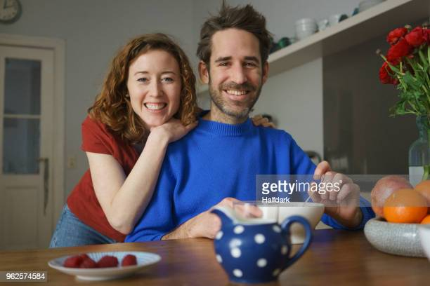 portrait of smiling mid adult couple at table with breakfast in room - mid adult couple stock pictures, royalty-free photos & images