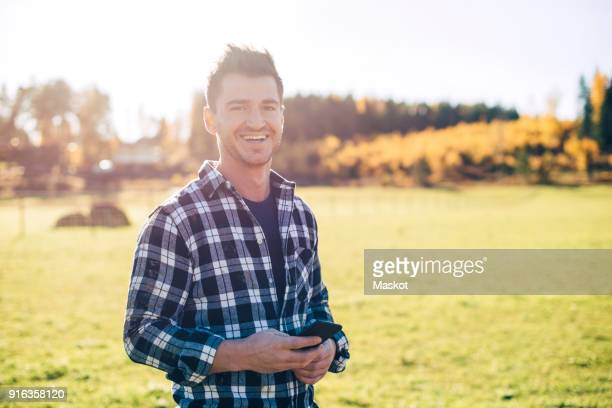 portrait of smiling mid adult male farmer holding mobile phone while standing on field - noord europa stockfoto's en -beelden