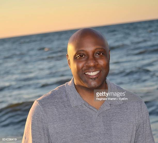 Portrait of Smiling Mid Adult Man Against Sea At Beach