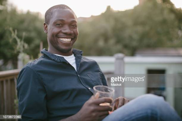 portrait of smiling mid adult man holding glass while sitting at porch - one man only stock pictures, royalty-free photos & images